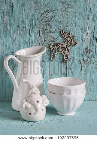 white vintage crockery - enamelled jug, ceramic bowl and white ceramic Santa Claus on blue wooden su