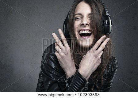 Laughing Young Woman With Head Phones Listening To Music Against Dark Wall Background