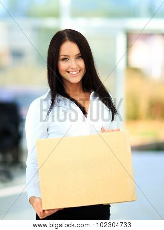 Closeup portrait of pretty adult woman holding a box at office building