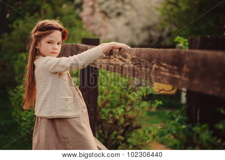 adorable dreamy child girl on the country walk at rustic wooden fence, soft vintage toning