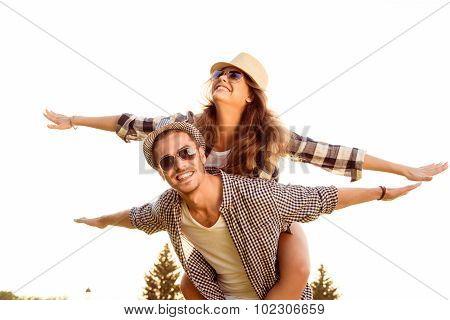 Happy Young Man Piggybacking His Girlfriend.