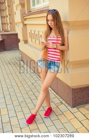 Leggy Girl Looks In Her Phone On The Street