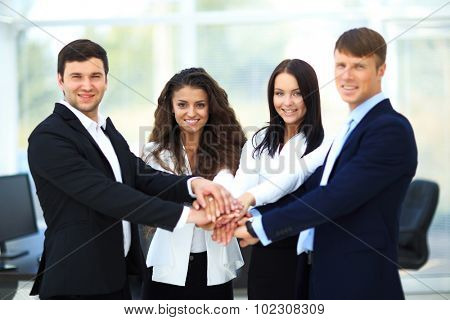 Group of business people piling up their hands together in the workplace