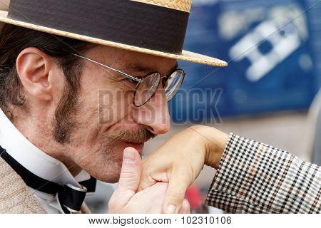 Man In Straw Hat Kissing Elegant Lady's Hand