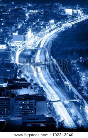 Night road with motion traffic in residential district, city life, Istanbul, Turkey - blue toned