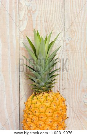 Closeup of a fresh ripe pineapple against a rustic white wood background. Vertical format with copy space.