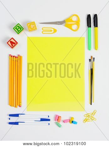 A variety of school supplies arranged around a sheet of blank yellow paper. Vertical format with copy space