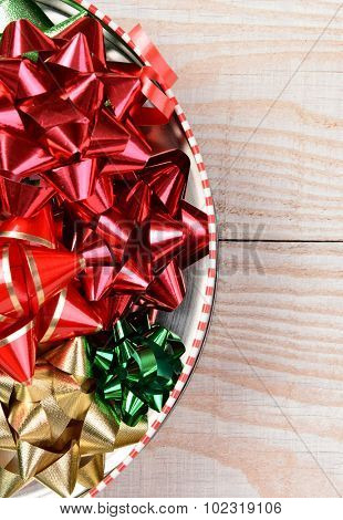 High angle view of a tin full of holiday bows. Vertical format on a white board background with only half the tin shown and copy space.