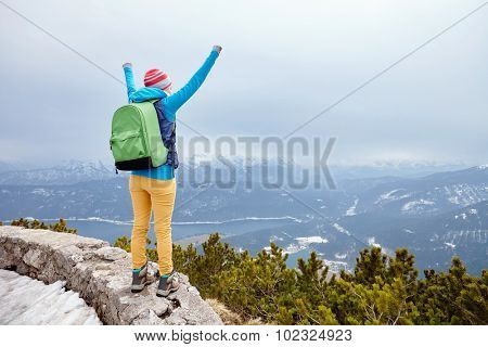 Back view of young woman wearing pink hat, blue jacket, green backpack, yellow pants and hiking boots raising her hands against winter mountain valley celebrating successful climb - goal concept