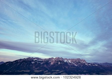 Mountain landscape with snow capped tops of alpine sierra against moody sky