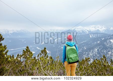 Back view of young woman wearing pink hat, blue jacket, green backpack and yellow pants standing against winter mountain valley - adventure concept