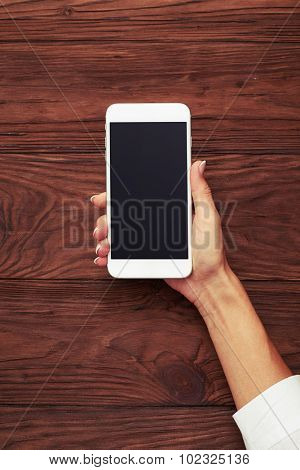 view from above on womans hand with smartphone over wooden background