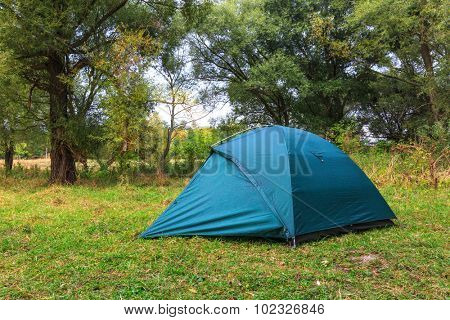 Scene with tourist tent on meadow in forest