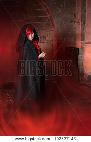 Foggy scene with a beautiful vampire gothic woman in a medieval abbey