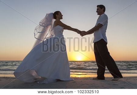 A married couple, bride and groom, sunset sunrise wedding on a beautiful tropical beach