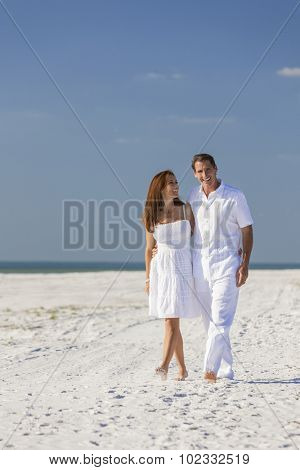 Romantic man and woman romantic couple in white clothes walking on a deserted tropical beach with bright clear blue sky