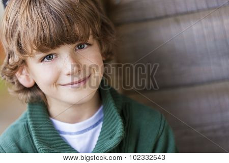 Young happy smiling boy outside wearing a a green jumper