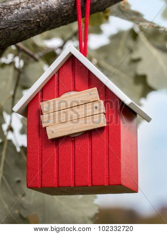 Wooden red birdhouse hanging on tree branch with entry hole covered with planks