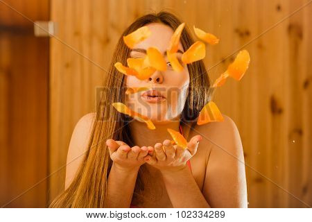 Carefree Young Woman Blowing Petals In Sauna.