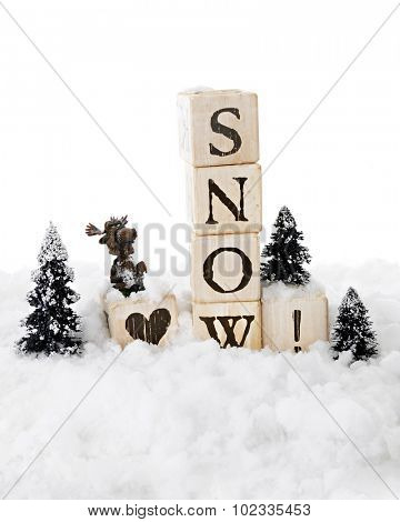 Snow-surrounded rustic alphabet blocks arranged with a heart before