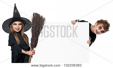 Little boy and girl wearing halloween costume with broom and blank board on white background