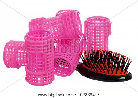 Pink hair curlers and hairbrush isolated on white background