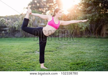 Young woman practicing yoga at a park