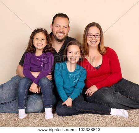 Family of four sitting in a livingroom