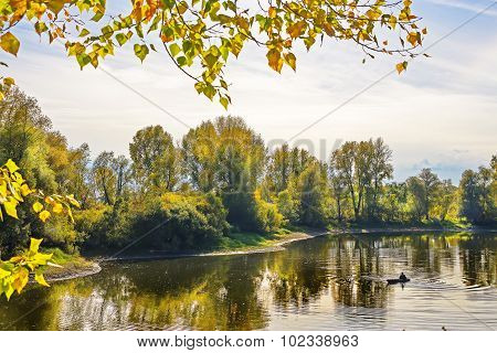 Autumn landscape with fisherman in a boat on the river