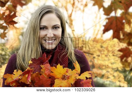 Autumn fall portrait of woman surrounded by colorful leaves