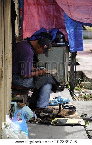Shoe repairer at Siti Khadijah Market in in Kota Bharu, Kelantan, Malaysia, Asia