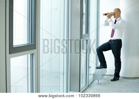 caucasian businessman spying using telescope thru office window
