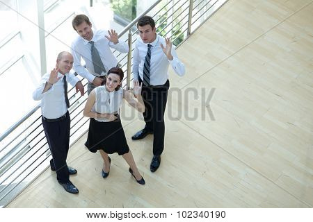 Businessmen and woman standing by railing with hands raised, portrait