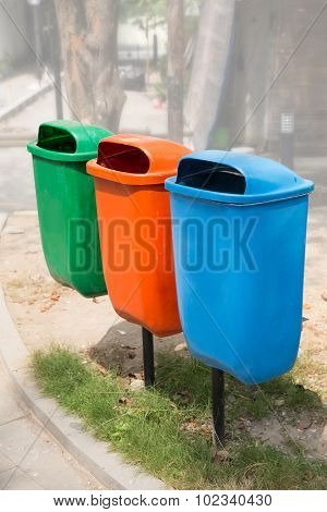 Three Trash Bin In Different Colors On A Park