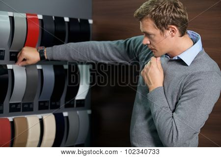 Young man looking at color swatch
