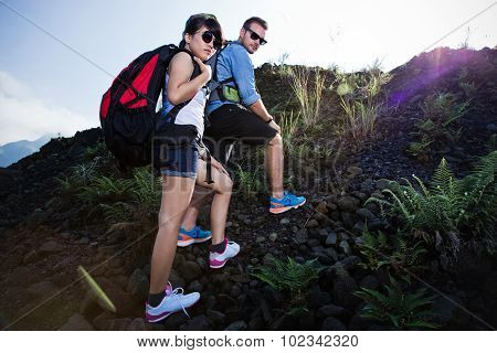 Mixed Race Couple Go Trekking Together, Walking On An Uphill,  Nature Background