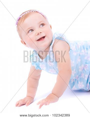 Cute joyful baby girl crawling in the studio,  sweet little child wearing nice dress and headband with curious looking up, isolated on white background, happy childhood concept