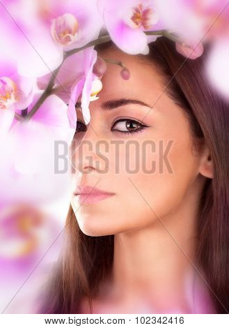 Closeup portrait of beautiful woman in amazing fresh orchid garden, gentle pink flowers around cute female face, enjoying day spa