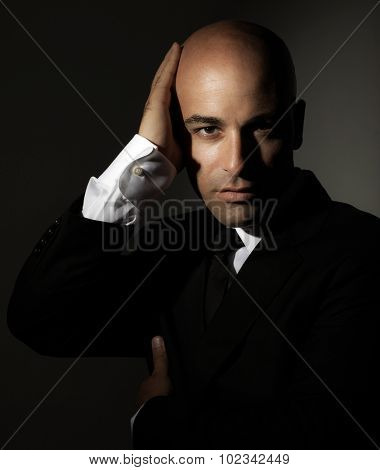 Portrait of beautiful handsome man wearing stylish suit isolated on black background, fashion for successful young men