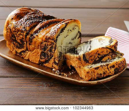 sponge cake with poppy seeds on a wooden plate
