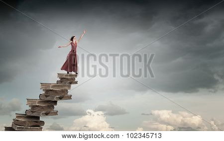 Woman in long dress with blindfold on eyes standing on pile of books