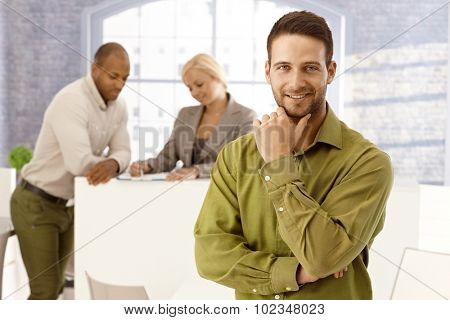 Portrait of handsome young businessman standing with hand on chin, smiling, looking at camera.