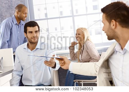 Businessman reaching out for folder handed by colleague.