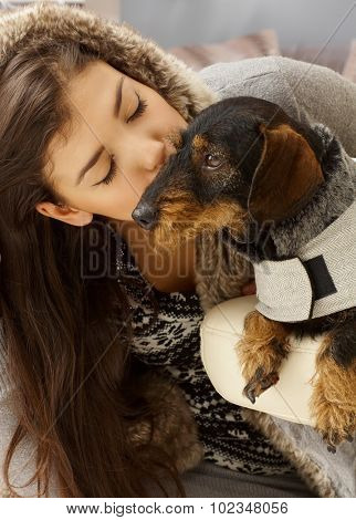 Young woman kissing dog eyes closed.