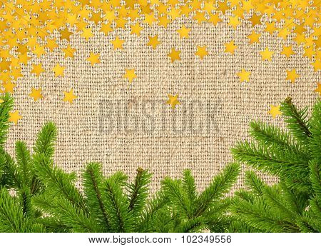 Green Christmas Tree Branch And Golden Stars On Linen Texture Background