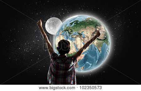 Back view of girl with hands up looking at planets. Elements of this image are furnished by NASA