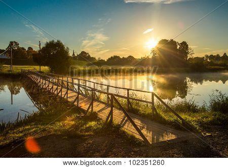 wooden bridge through river in morning sunlight.