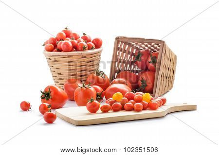 Various Types Of Tomatoes On Rattan Basket And Wooden Cutting Board