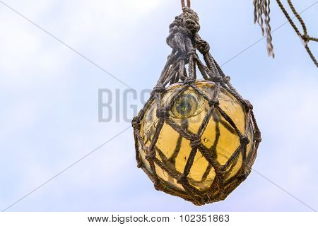 Historical Yellow Glass Fishing Float Ball Hanging In A Net To Dry