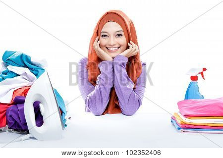 Young Smiling Woman Wearing Hijab Sitting Between Fresh Clean Laundry
